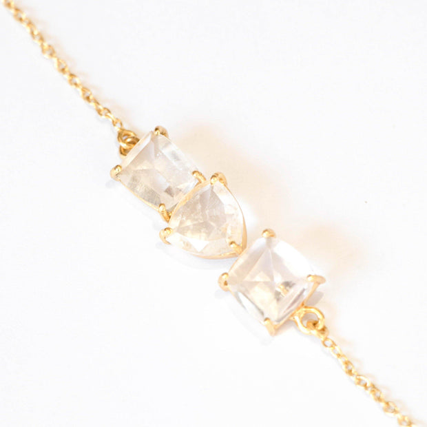 Three beautiful Crystal Quartz stones create a unique balanced bar style bracelet, set on a dainty gold-plated adjustable chain