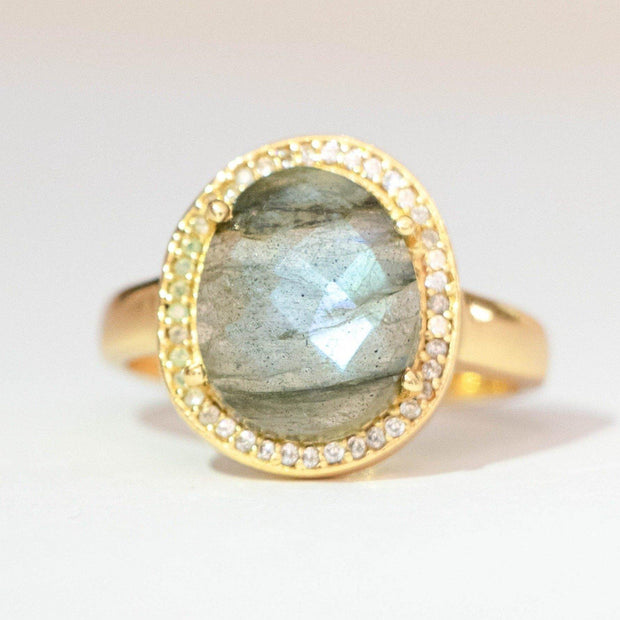This ring features a beautiful naturally shaped solitaire Labradorite stone that is surrounded by a halo of pave set cubic zirconias