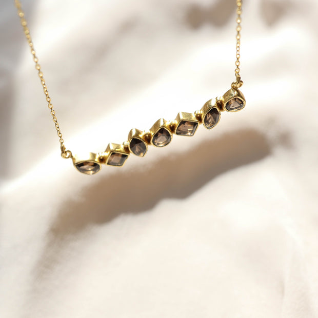 This unique Bar Necklace features a row of Smokey Quartz stones set in a bold bar style. Handmade in sterling silver and 14 carat gold plating