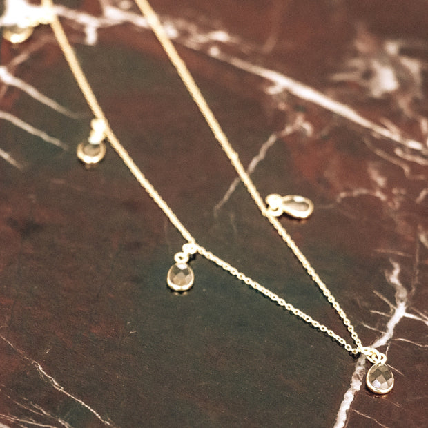 Our Smokey Quartz charm necklace features five stones delicately attached to a fine gold plated chain creating this easy to wear and lightweight necklace