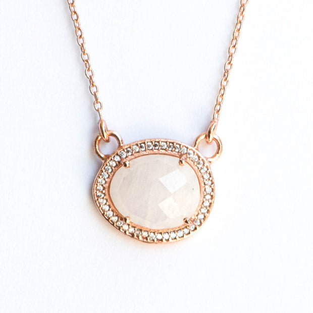 This beautiful pendant features a naturally shaped Rainbow Moonstone semi-precious gemstone surrounded by a halo of pave set cubic zirconias set on a dainty Rose Gold adjustable chain