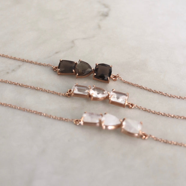 Three Smokey Quartz semi precious stones set on a dainty 14 carat rose gold-plated chain create a unique bar style bracelet