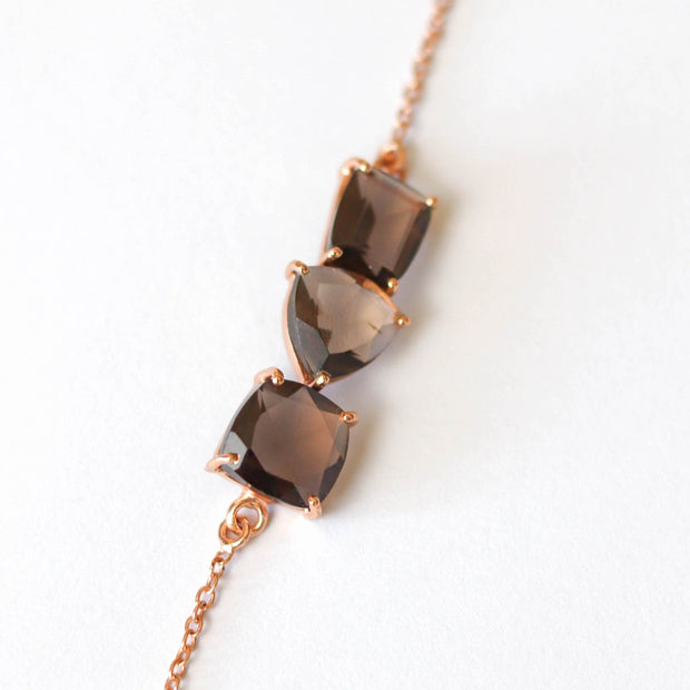 Three Smokey Quartz stones are each cut in unique shapes and placed together to create a unique balanced bar style bracelet. Set on a dainty rose gold-plated adjustable chain