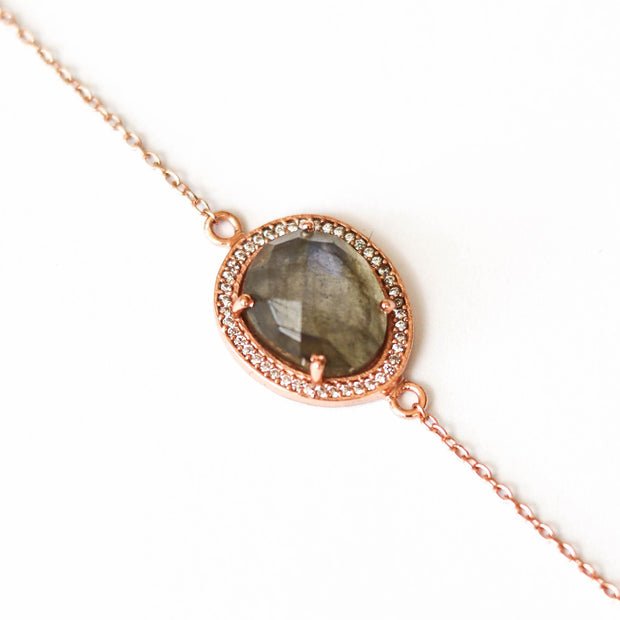 A beautiful Labradorite is surrounded by a halo of pave set cubic zirconias set on a dainty adjustable rose gold plated chain
