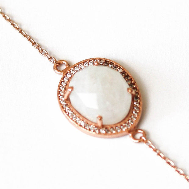 A beautiful Rainbow Moonstone surrounded by a pave halo of cubic zirconias set on a dainty adjustable 14 carat rose gold plated chain
