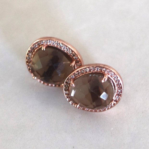 A beautiful pair of organic shaped Smokey Quartz stones are surrounded by a halo of pave set cubic zirconias