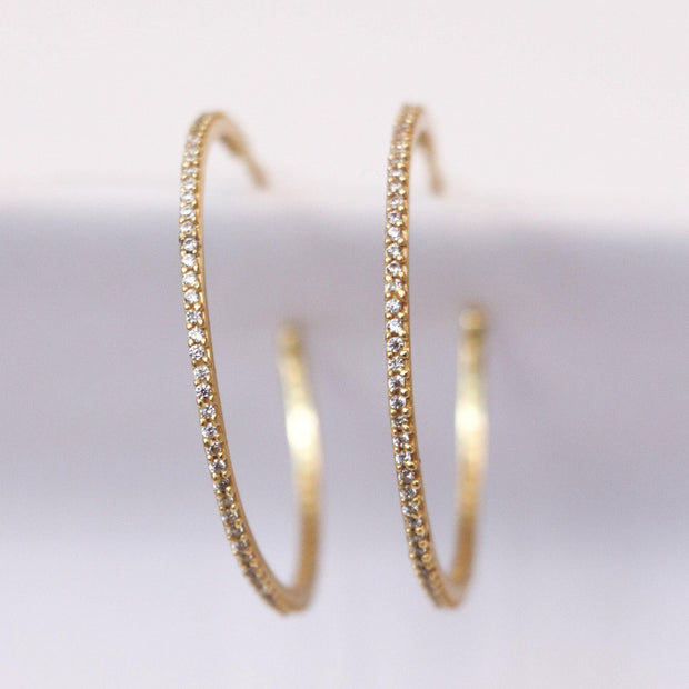 Simple, elegant and stylish. These easy-to-wear medium sized hoops are made in sterling silver 14 carat gold plating. Featuring small cubic zirconia stones set in a pave style