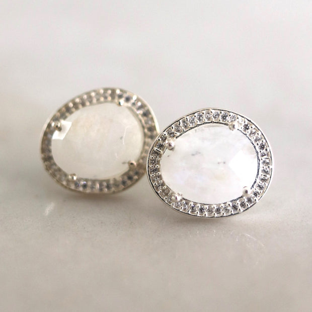 A pair of beautiful semi-precious Rainbow Moonstone stones set in a pave halo - adding a subtle finishing touch to your day or night look