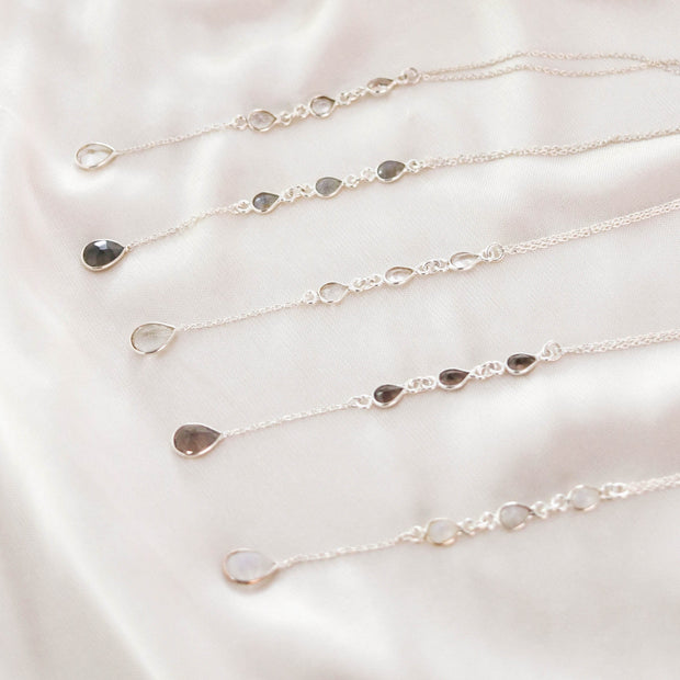 Dainty and elegant lariat necklaces feature four pear shaped gemstones. Available in semiprecious stone options Smokey Quartz, Moonstone, Crystal Quartz, Labradorite & Green Amethyst