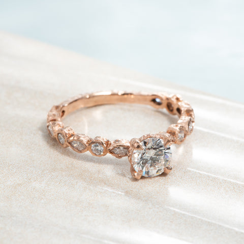 Recycled 14 karat rose gold wedding ring with 15 natural diamonds with a combined weight of 1.19 carats. This wedding band contains 8 marquise cut diamonds & 7 round side diamonds in which have been bezel set and a 0.74 carat GIA certified centre stone in a 4 prong setting with a rough texture.