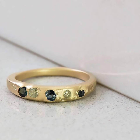 Recycled 14 karat yellow gold set in cast Kimberlite ring with five natural recycled sapphires brought to a satin finish.