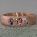 Recycled 14 karat rose gold Kimberlite ring with three oval sapphires (2 violet & 1 pink) in which have a total wight of 0.58 carats in which have been set in cast. The ring has a tapered half round profile in which ranges from 5mm at the top to 3mm at the bottom of the ring.
