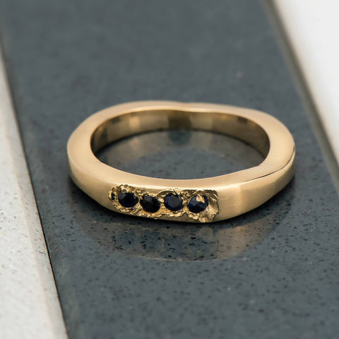 Recycled 14 karat yellow gold signet ring with four 2mm natural blue sapphires in which have been set in cast, casted. The surroundings of the stones have been finished with a rough baroque texture and the band is an irregular shape.