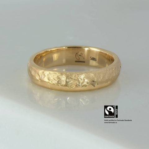 14 karat Fairtrade Certified gold wedding ring with a pitted texture on one side & polished bevel on the other. The ring is a half round profile measuring 5mm in width & 1.8mm in thickness.