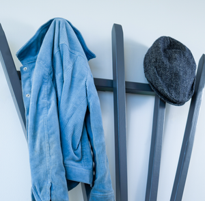 A contemporary wooden coat rack with 5 long hooks to hold your clothes as well as an attached  shelf that can hold your knit knacks like your keys and phone.