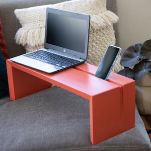 A portable office desk holding a laptop and phone on top of a grey contemporary couch.