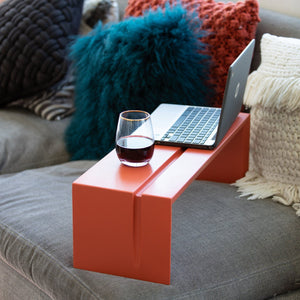 A portable office desk holding  a laptop and a glass of wine  sitting on a contemporary couch.