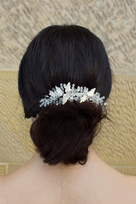 Crystals and Silver Leaves Bridal Clip worn by a brown haired model with a stone wall background