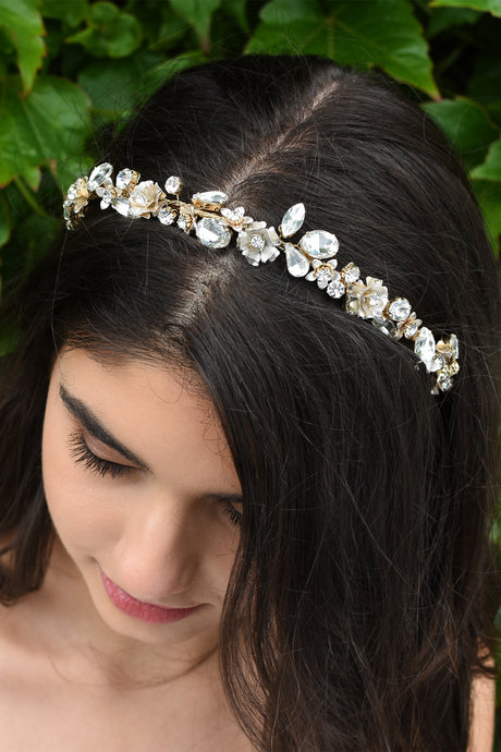 Dark hair smiling Bride wearing a thin headband full of different shapes of stones with green leaves in the background