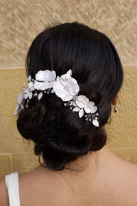 Black haired bride wears a white bridal clip in front of a sandstone wall