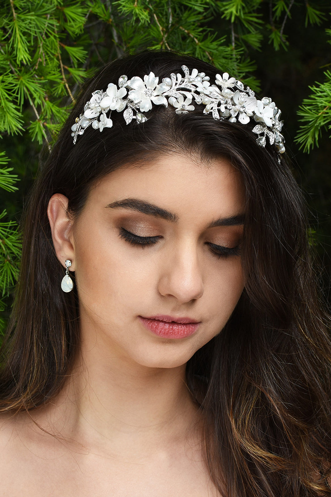 A dark hair bride wears a silver flowers and leaves headband with green leaves background