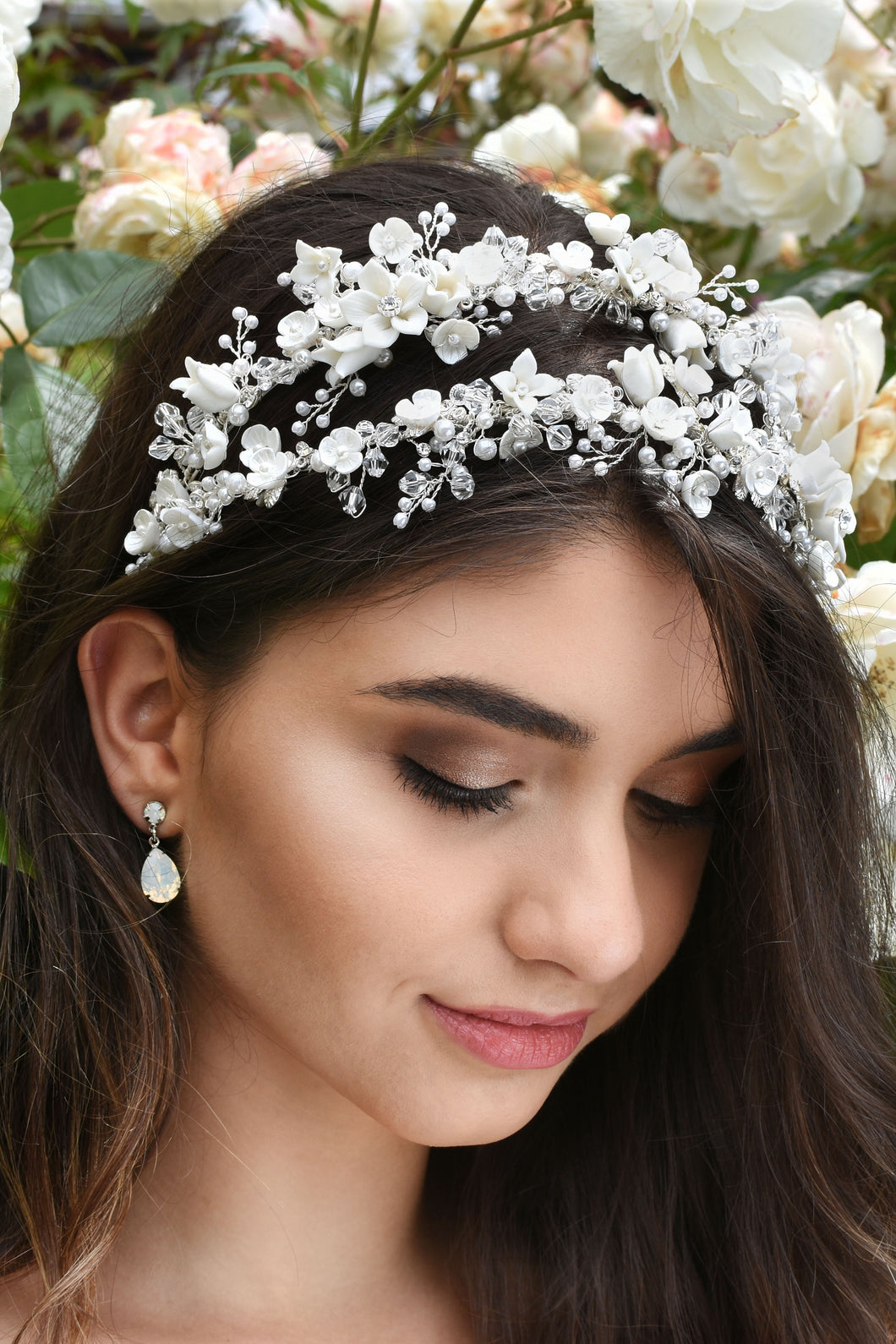 Dark hair bride wears a double row headband of ceramic flowers with a background of white roses