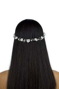 Model with long black hair wears a single strand flowers bridal vine with a white background