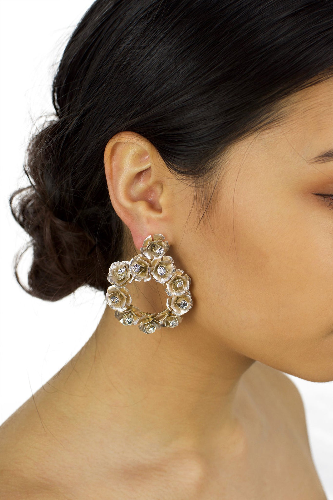 Ring of pale gold flowers earring worn by a bride with up style hair