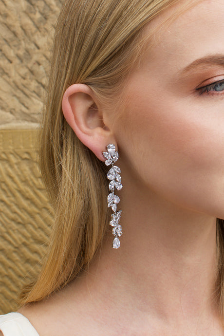 Long thin silver earring with stones worn by a blonde model with a sandstone wall backdrop