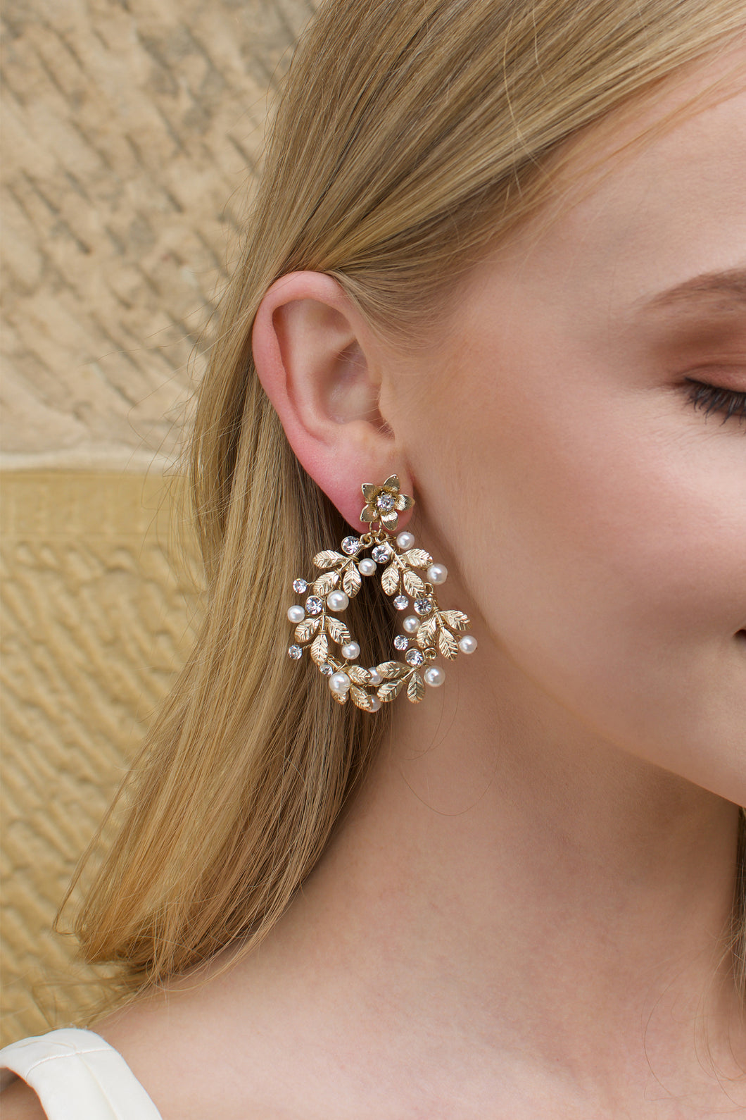 Large hoop shape gold earring worn by a blonde model