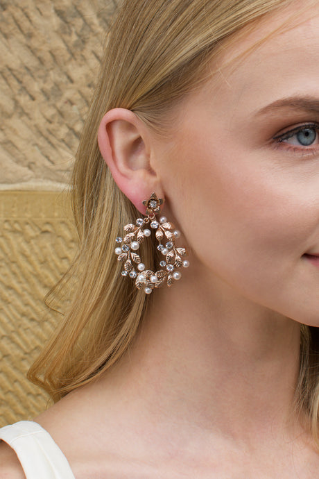 Model with blonde hair wears a rose gold hoop earring with pearls with a stone wall backdrop
