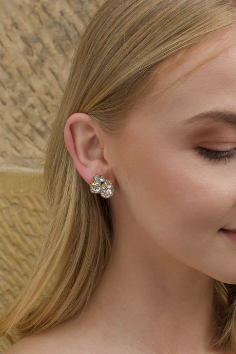 Clear stones in a gold hand made earring worn by a blonde model bride
