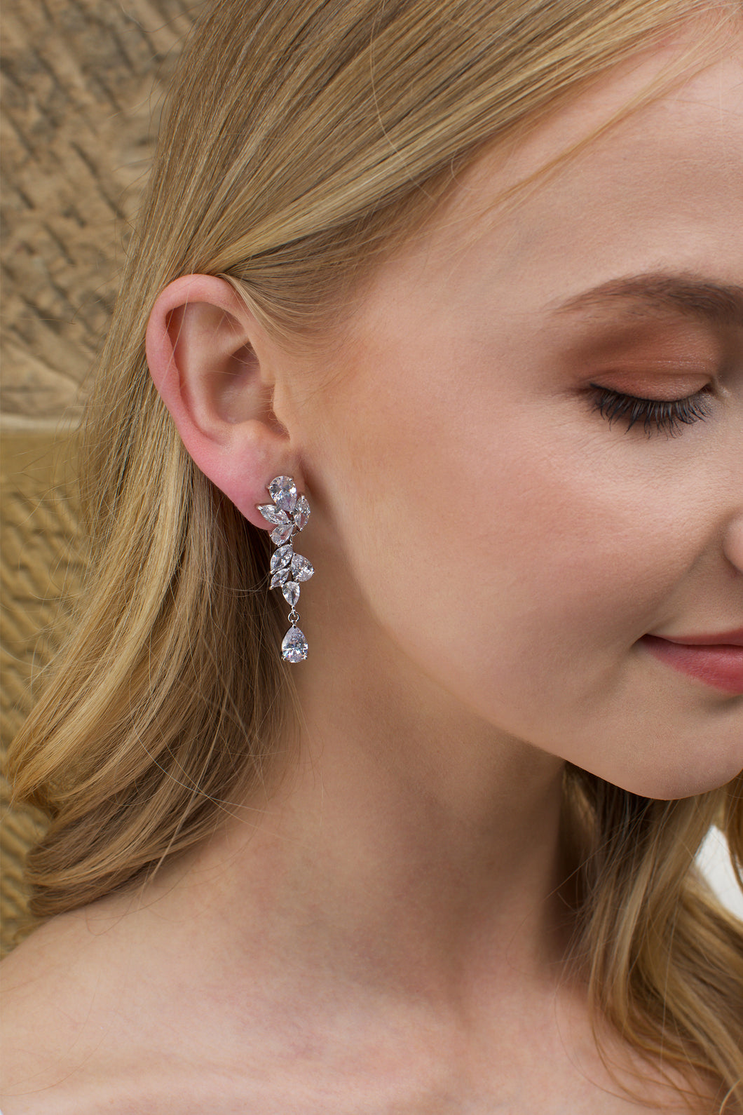 Blonde Model wearing a silver mid length earring with a stone wall backdrop