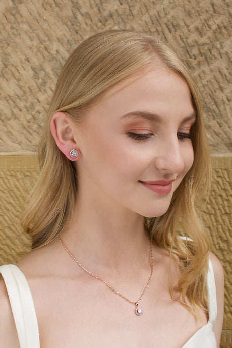 Model wears a simple rose gold chain with a single stone pendant with a stone wall background