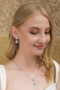 Blonde Bridal Model wearing a short pear shape drop earring with a sandstone backdrop