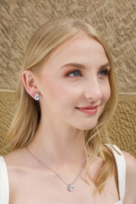 Blonde model wears a crystal teardrop earring and necklace set. A Sandstone wall is the background
