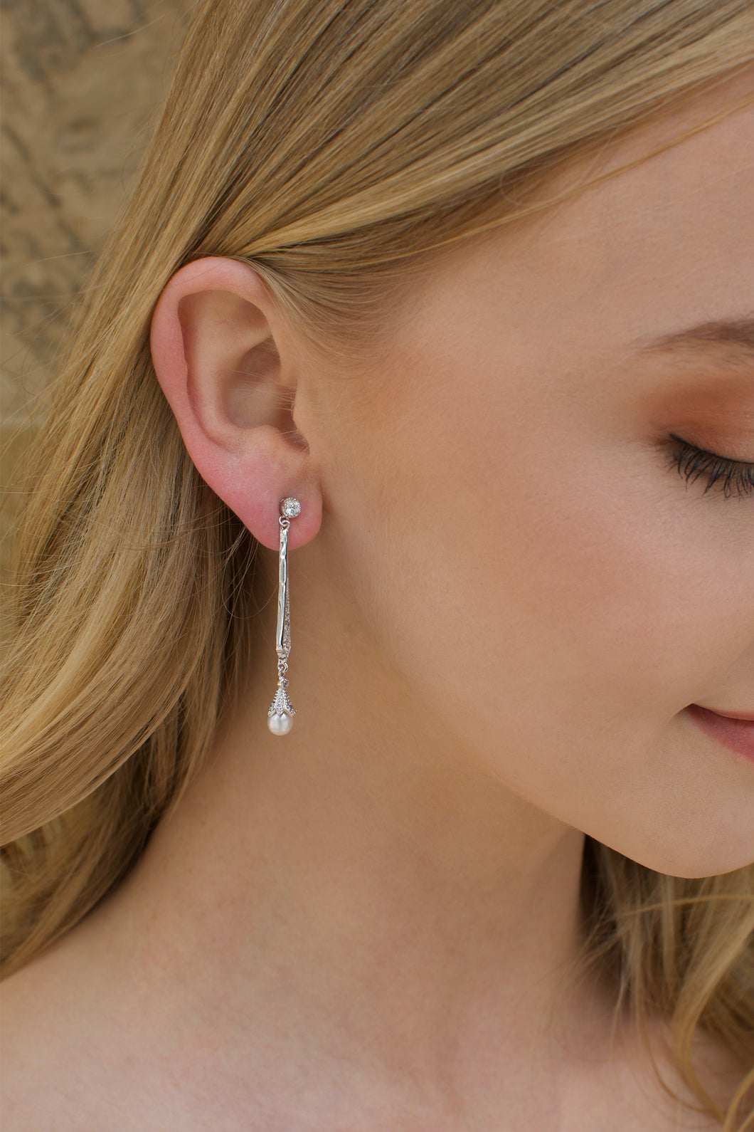 A long silver bridal earring with a hanging pearl worn by a blonde model