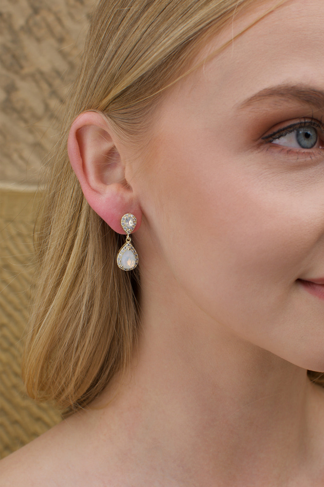 A blonde model wears a gold and white opal earring with a stone wall background