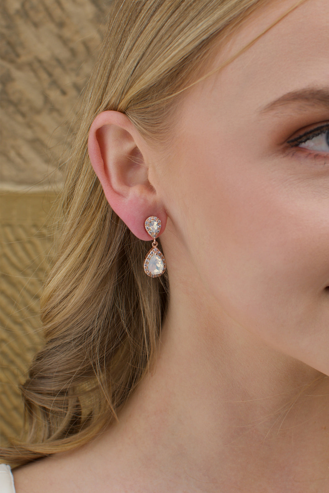 A blonde model bride wears a double teardrop earring with white opal colour stones