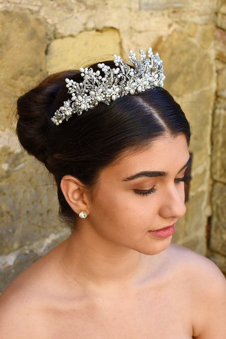 Dark haired model wears a pearl and silver tiara with a stone wall background