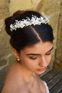 White and silver Bridal headpiece is worn by a dark hair model with a stone wall backdrop