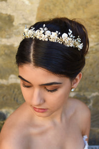 A model bride wears a pale gold bridal headband on her dark hair with a stone wall background