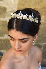 Load image into Gallery viewer, A model with dark hair wears a very pale champagne gold bridal tiara with a stone wall background