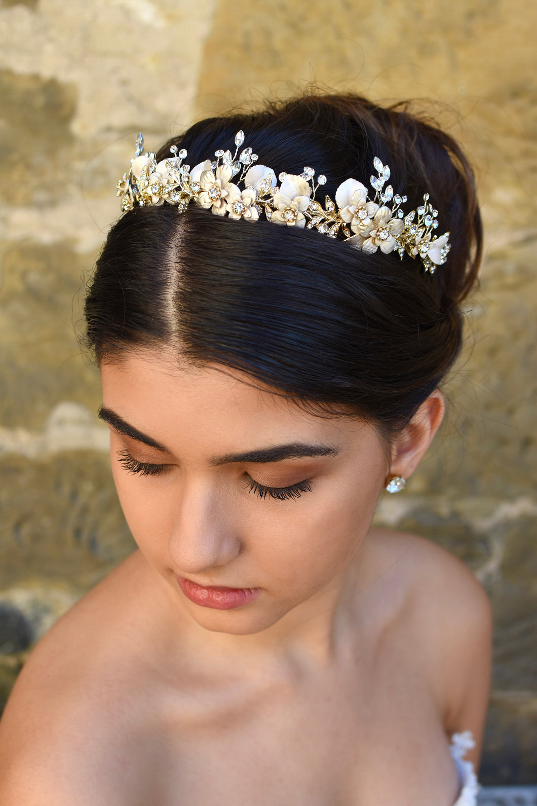 A model with dark hair wears a very pale champagne gold bridal tiara with a stone wall background