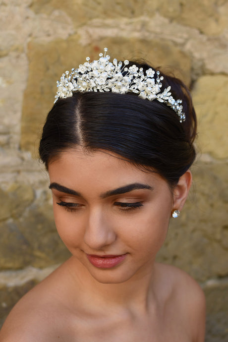 A dark haired model wears a silver tiara with pearl flowers against a stone wall