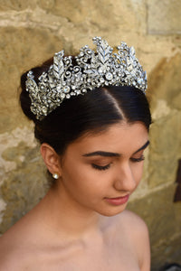 A High Bridal Crown with tall peaks worn by a dark bride with a stone wall backdrop