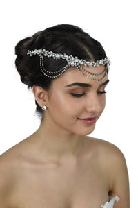 A bride wears a pearl and rhodium vine with loops on her forehead with a white background