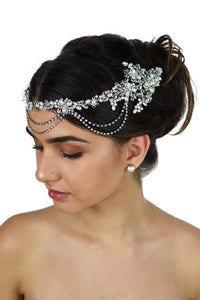 A dark hair model with her hair up wears a pearls and rhodium bridal vine at the front of her head. With a white background