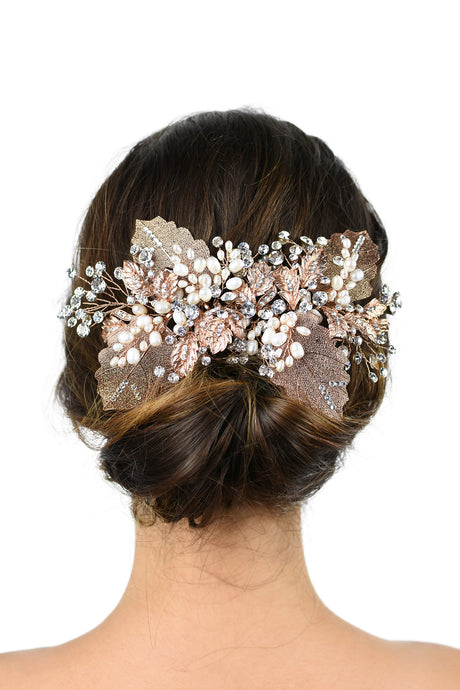 Brown hair model bride wears a large leaves bridal headpiece at the back of her head on a white background
