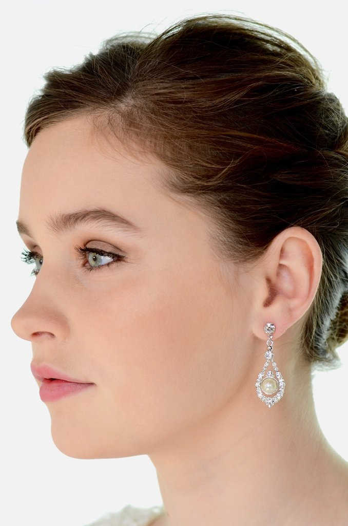 A green eyed model wears a pearl drop earring against a white background